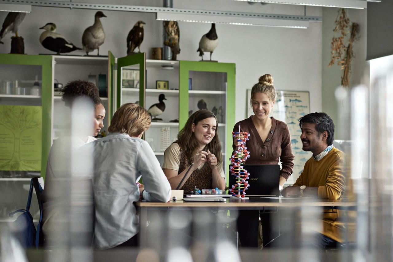 Fem unge mennesker omkring et bord