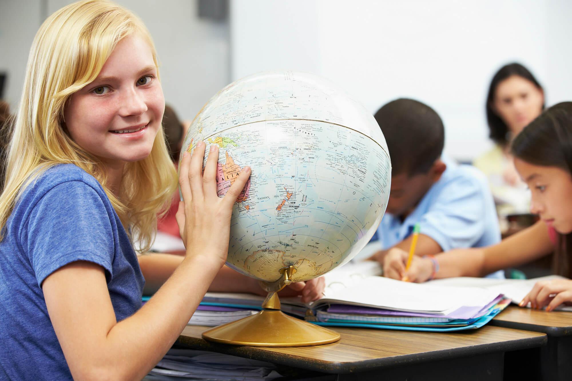 En skoleelev sidder med en globus i et klasselokale
