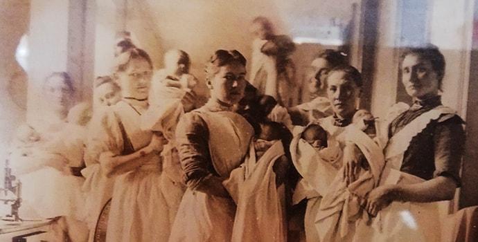 Historisk sort/hvid billede fra jordemoderuddannelsens start. Syv jordemødre står med babyer