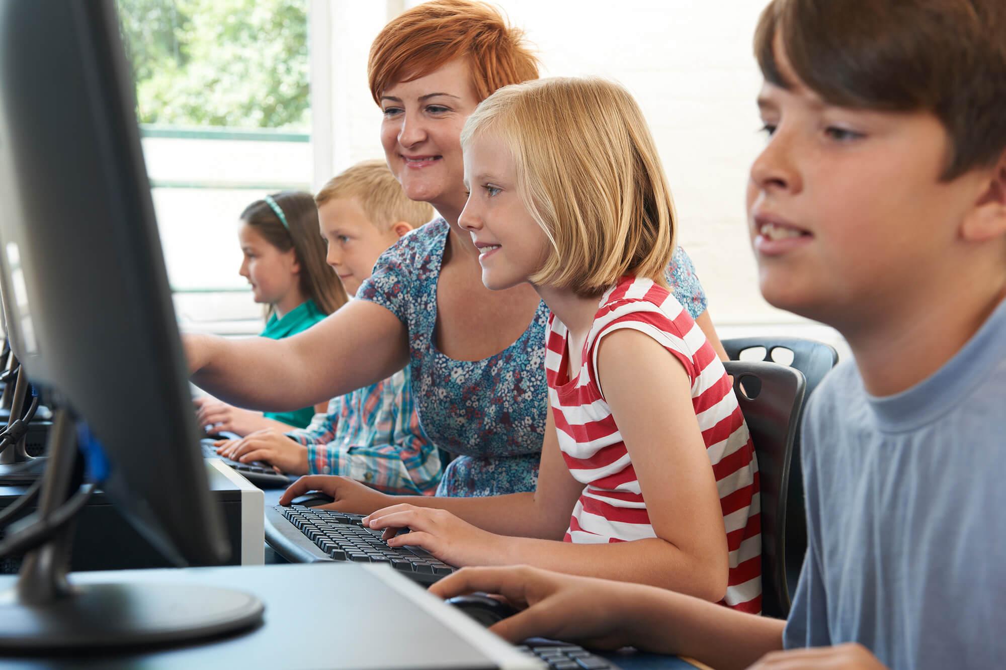 Fire børn og en lærer kigger på en skærm på en computer
