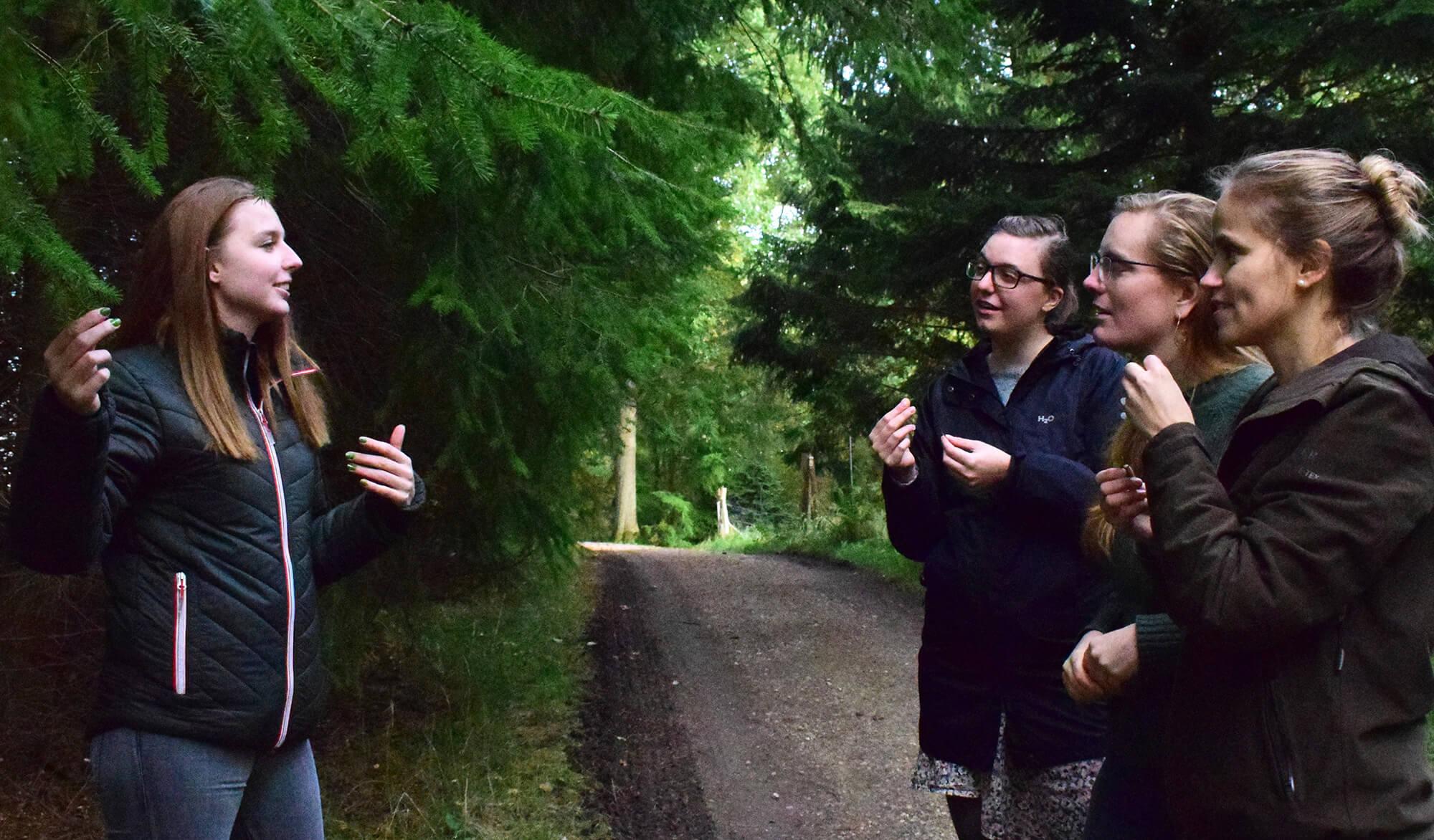 En natur- og kulturformidler guider og fortæller for tre gæster i skoven
