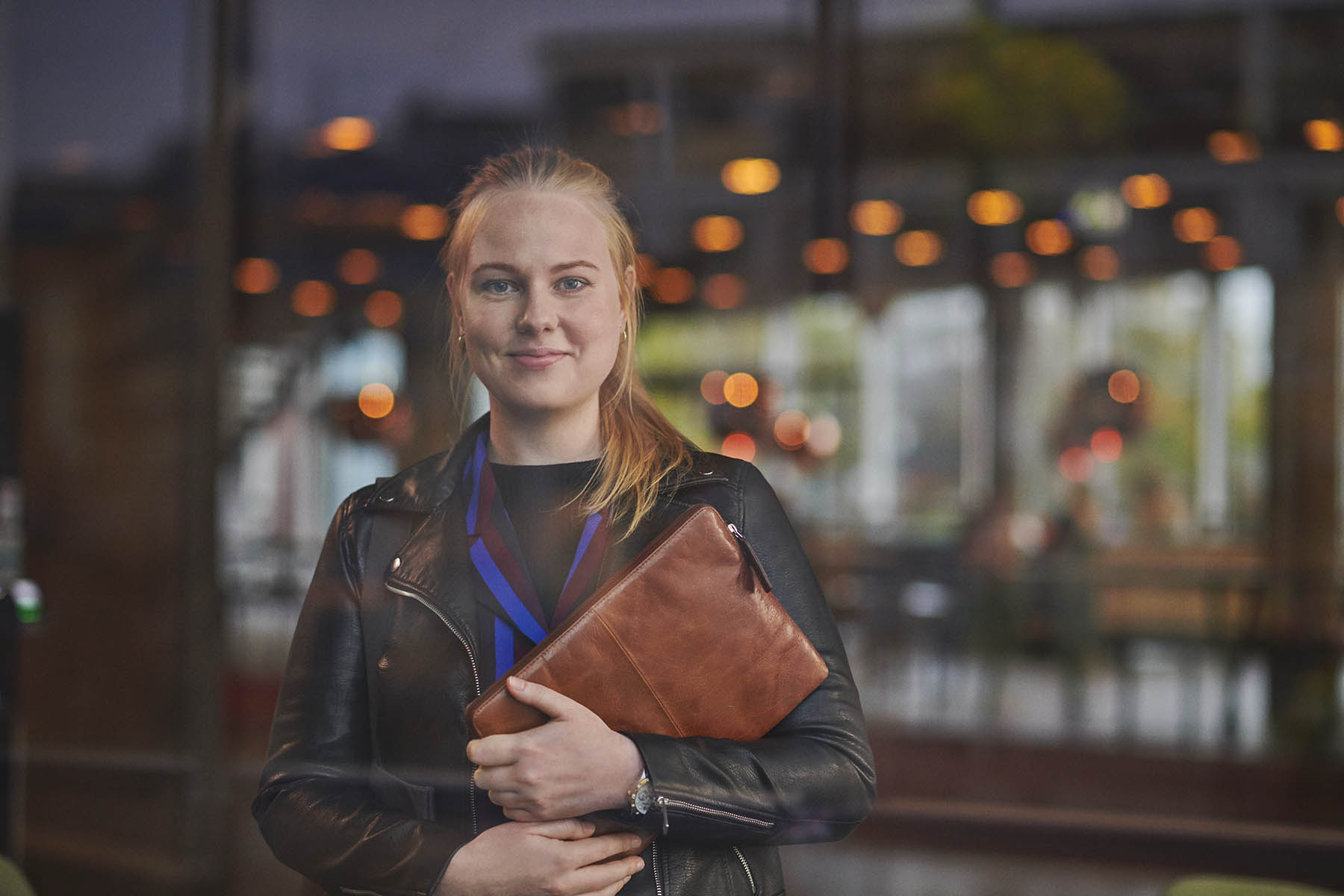 Administrationsbachelor - studerende på Købehhavns Professionshøjskole med taske ses gennem en rude