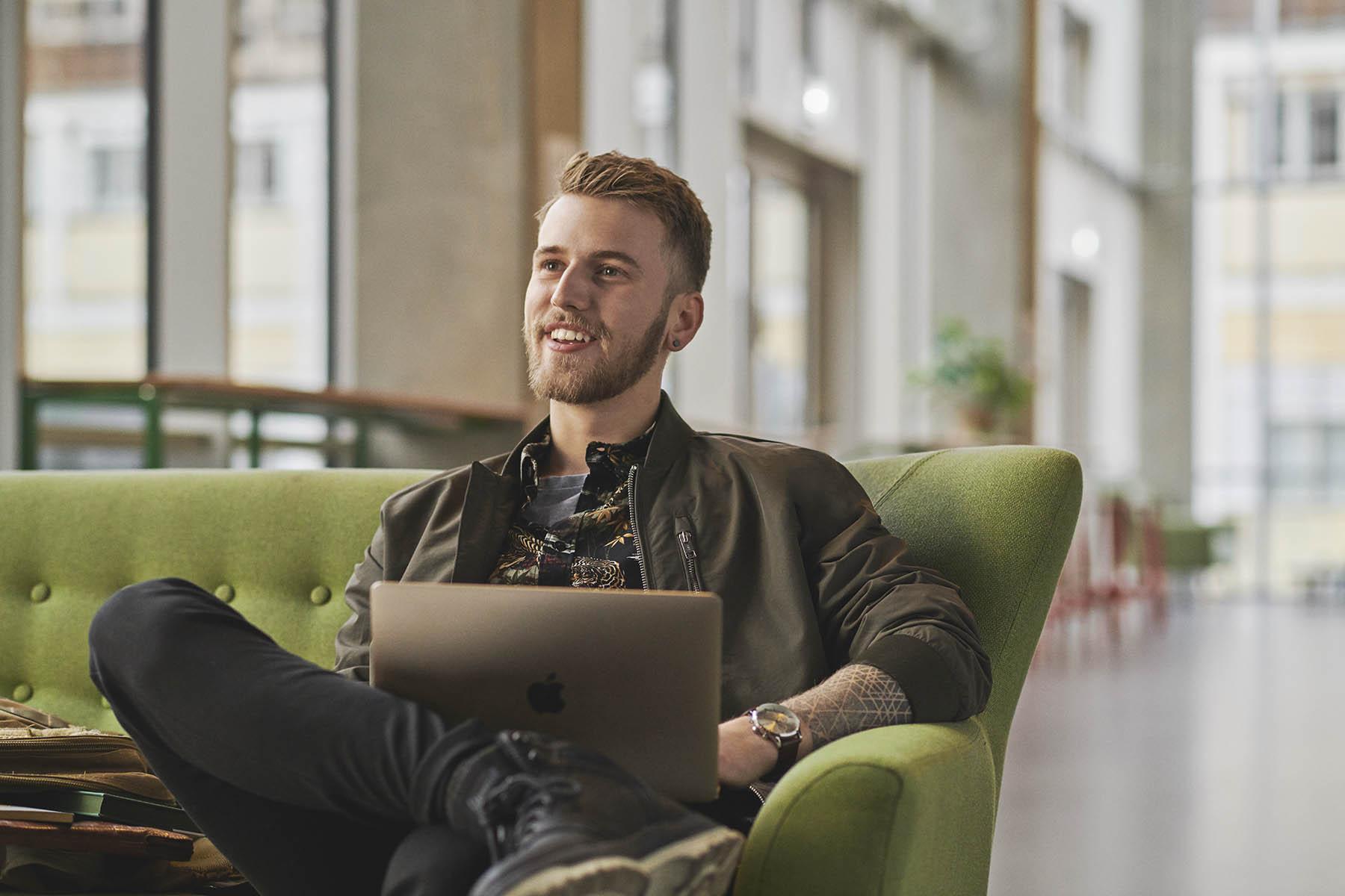 Administrationsøkonom på Københavns Professionshøjskole - fyr sidder i sofa med sin computer