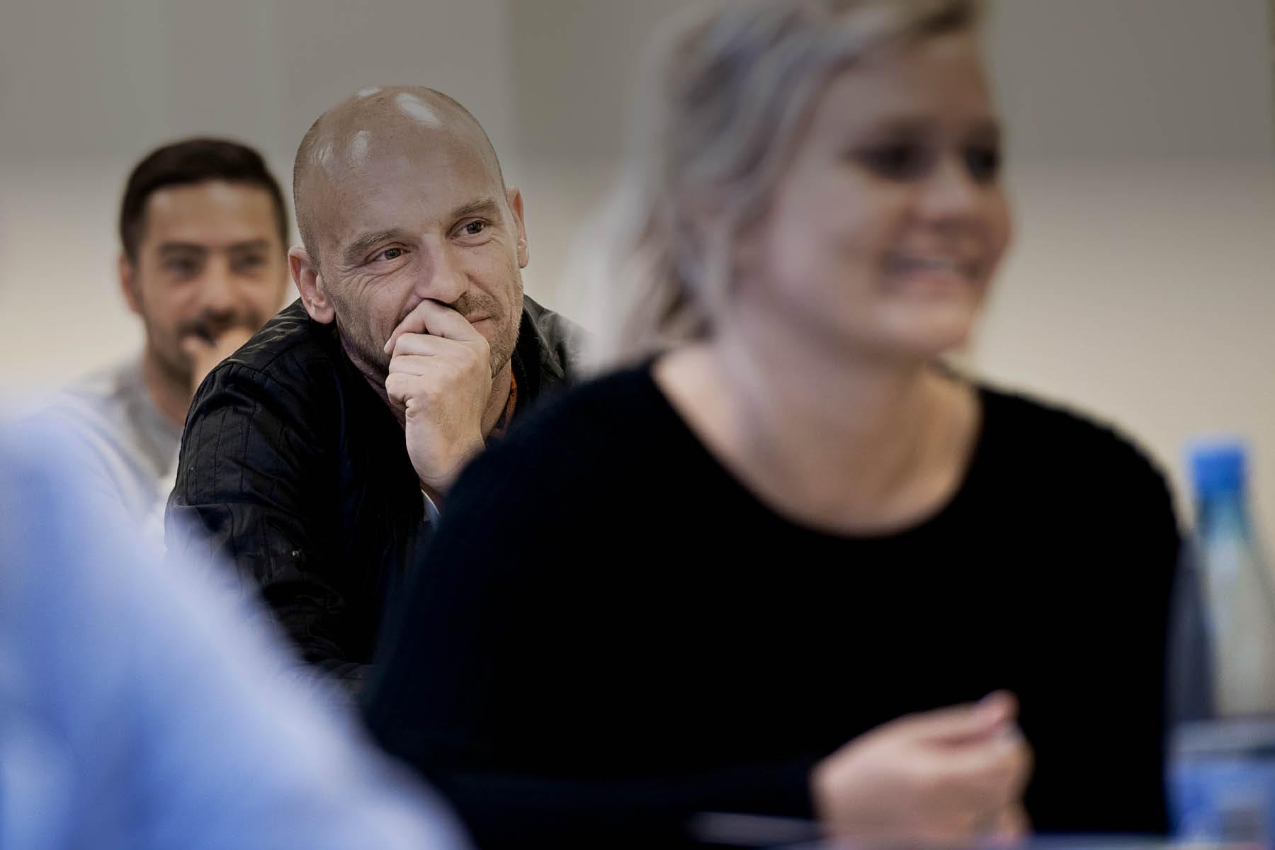 Voksen mand ser tænksom ud i et undervisningslokale