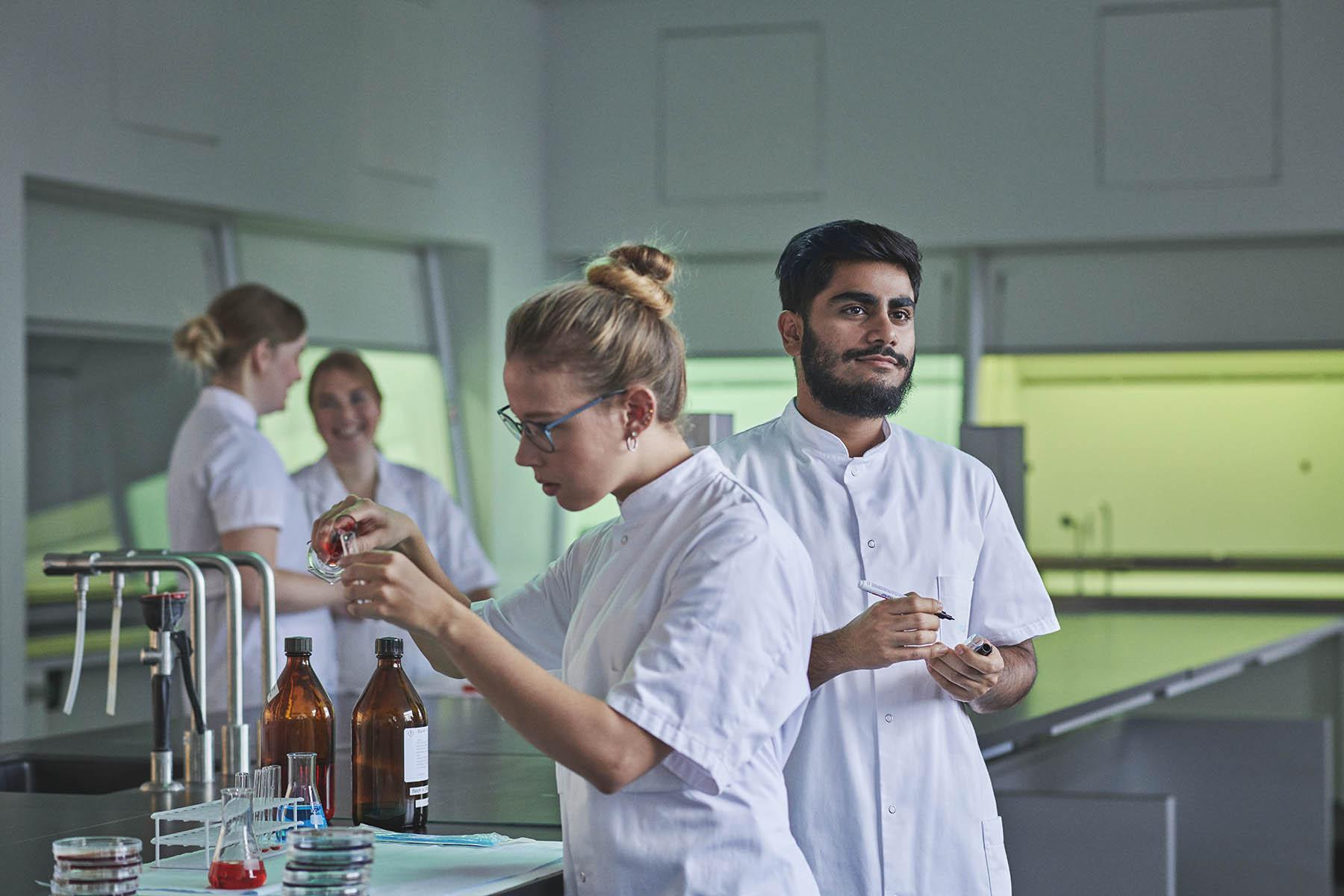 4 bioanalytikere-studerende på Københavns Professionshøjskole står i kitler i laberatorium og blander forskellige væsker.