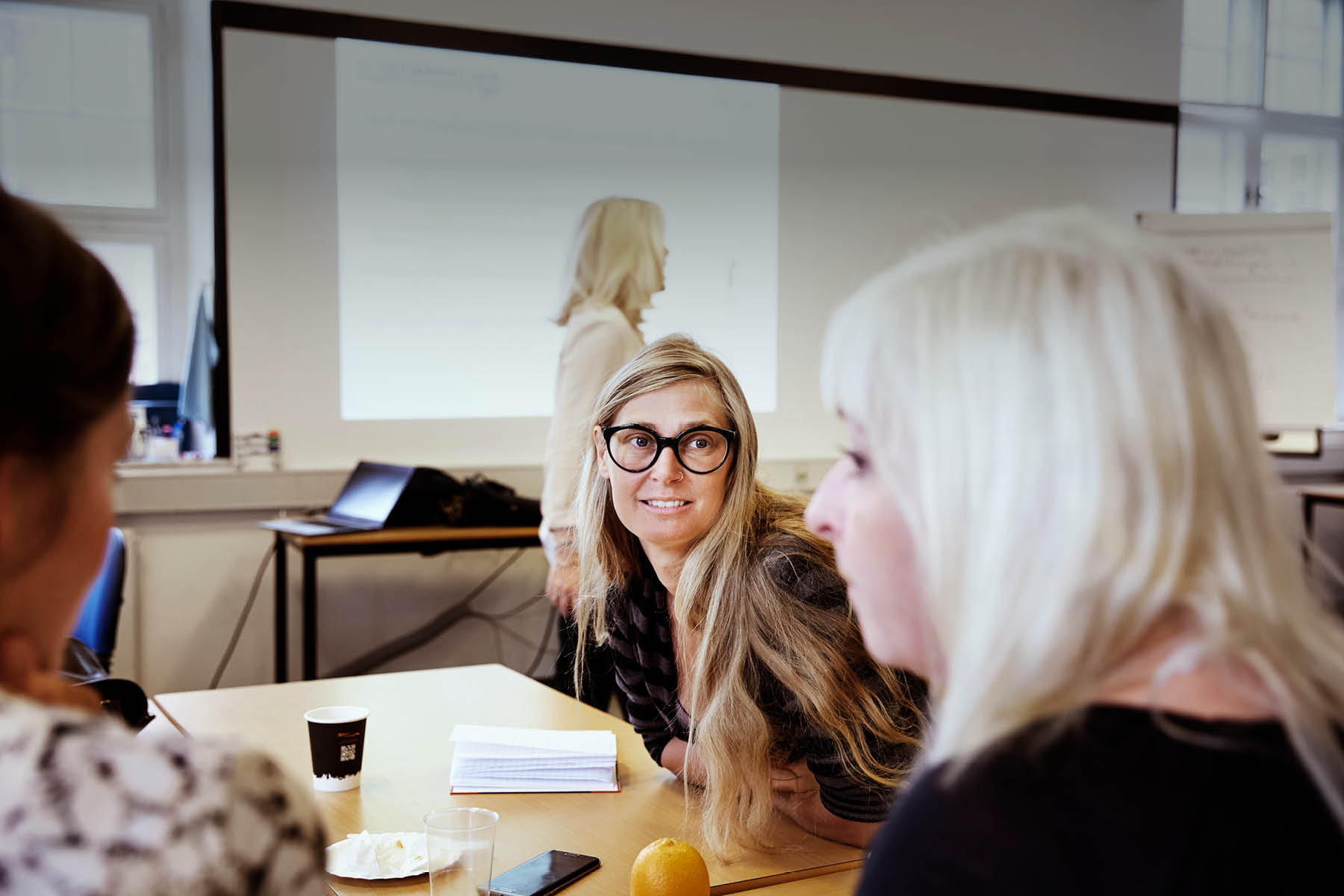 Kvinde sidder og løser gruppearbejde til undervisning i et klasselokale