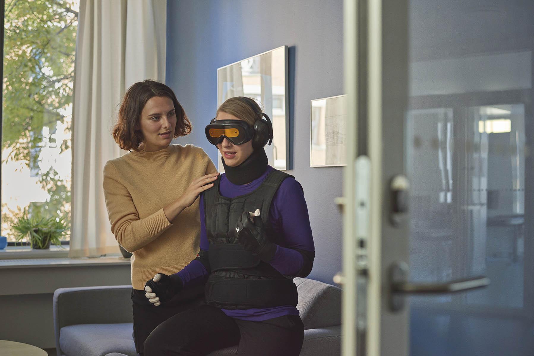 En ergoterapeutstuderende guider en person, som er iført en bevægelseshæmmende dragt