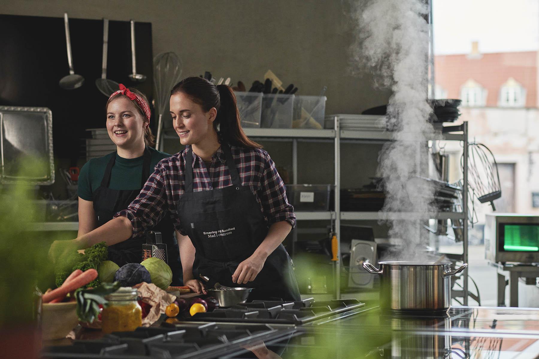 To studerende laver mad i et køkken