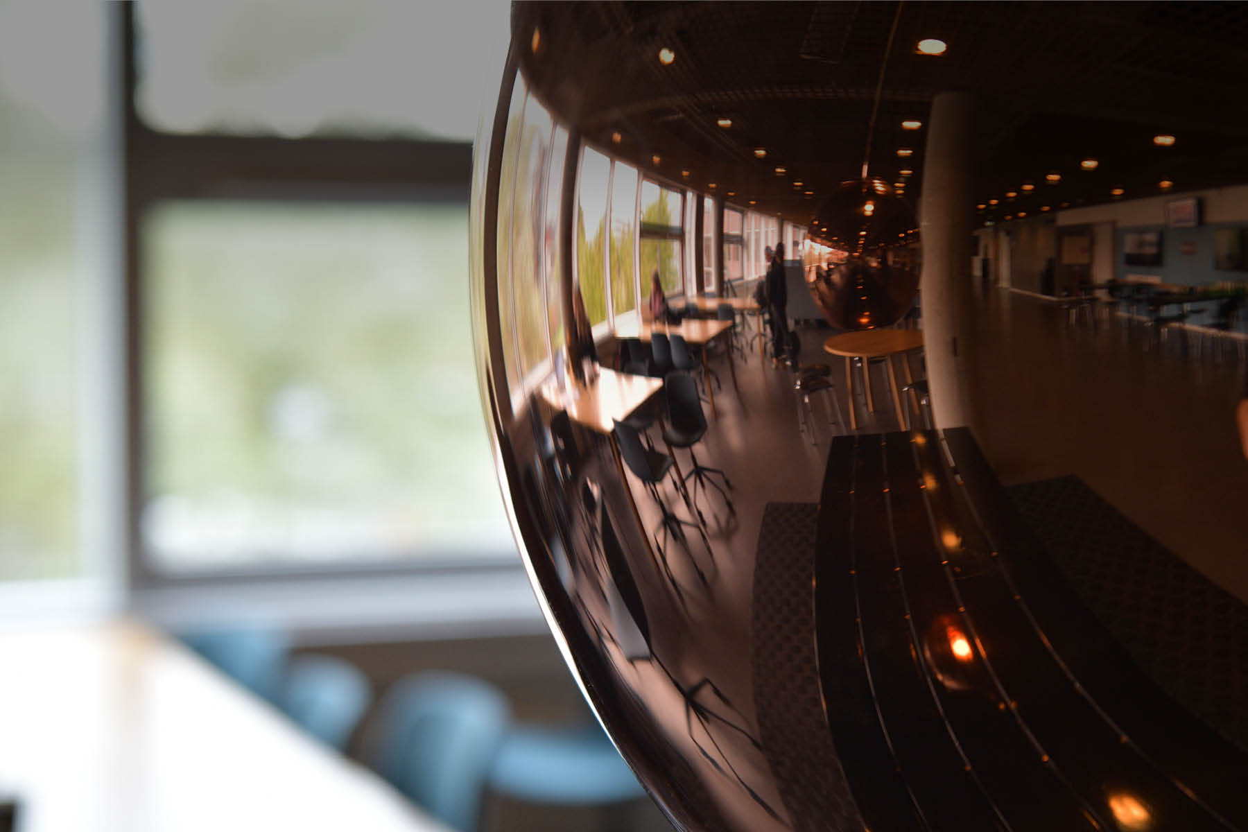 Der er fokus på en messinglampe på Campus Sigurdsgade - i lampens skær kan man se flere studerende arbejde i baggrunden
