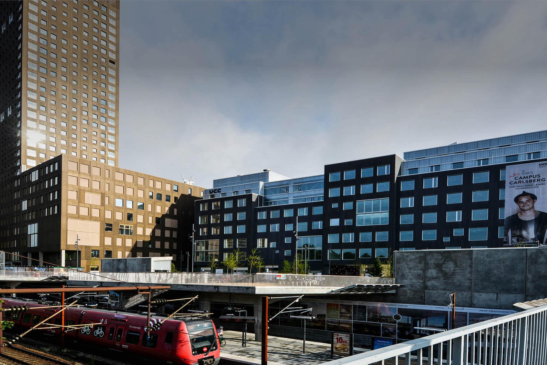 Campus Carlsberg ses fra siden der vender ned mod Carlsberg station, hvor der holder et s-tog.