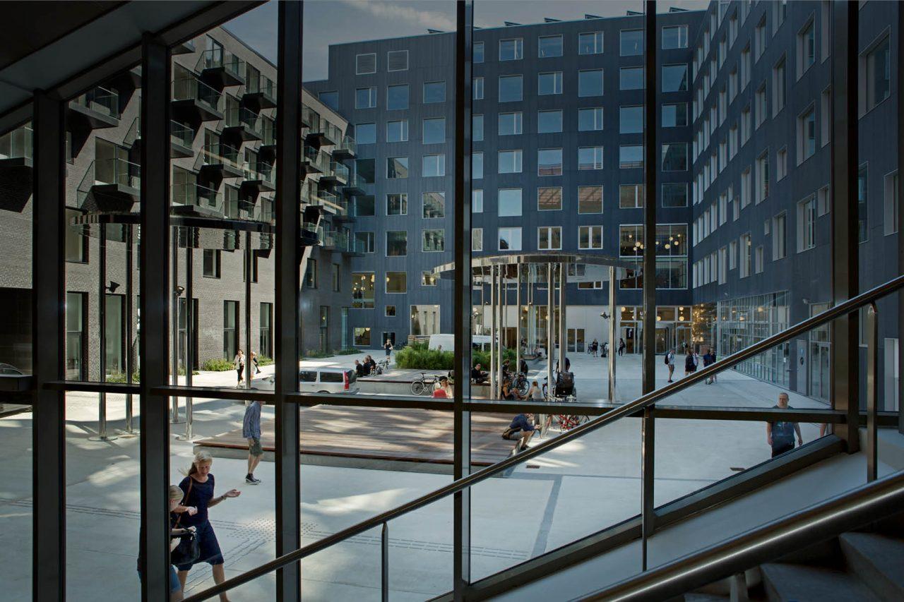 Der er mange mennesker og aktiviteter på torvet mellem bygningerne på campus carlsberg, som her ses gennem glasfacaden.