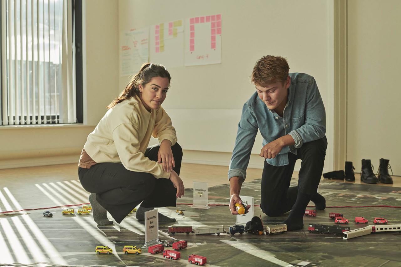 To studerende organiserer en indsats på en modelbane med beredskabsbiler
