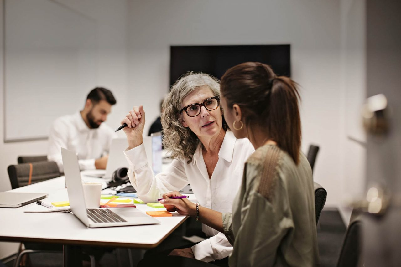 Konsulenter diskuterer og ideudvikler på post-its og en computer