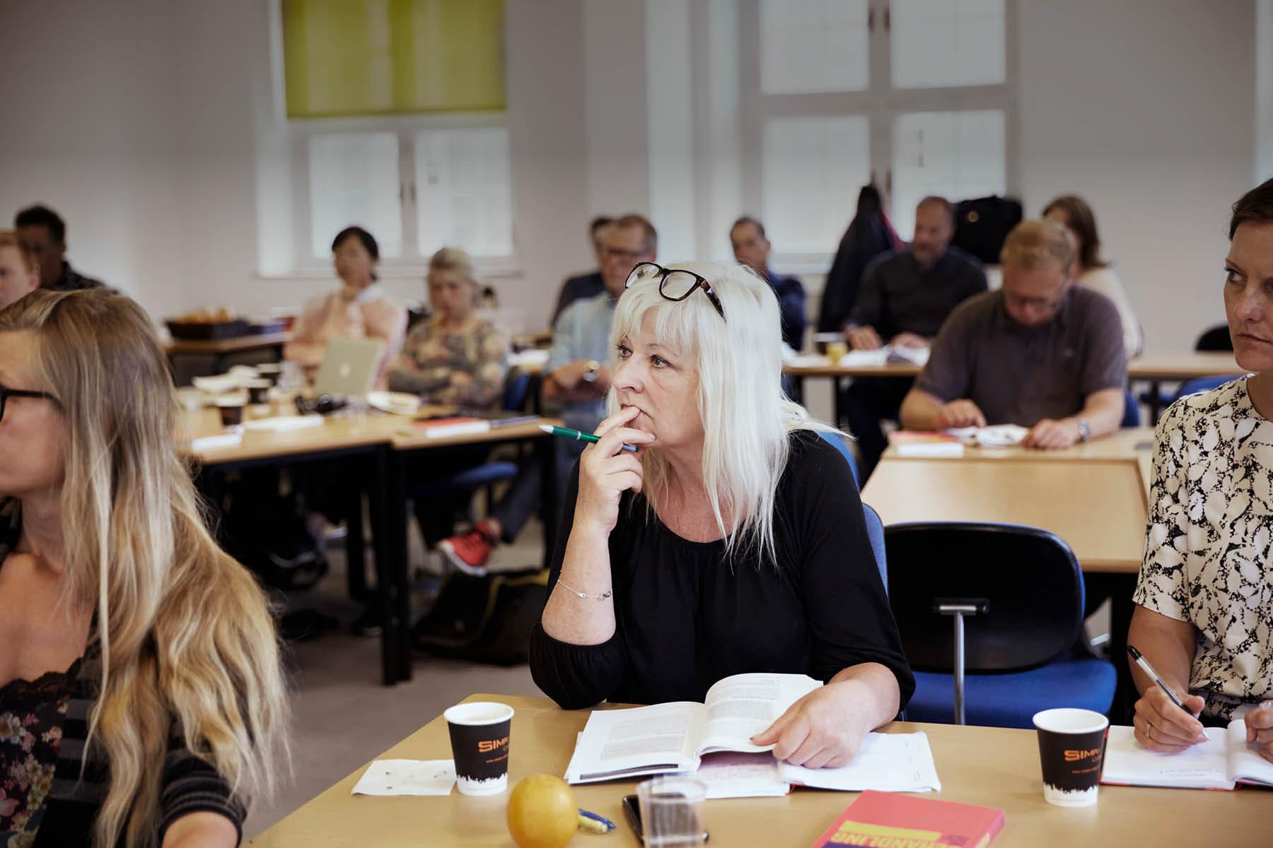 Voksen dame skriver noter, mens hun sidder til undervisning i et klasselokale