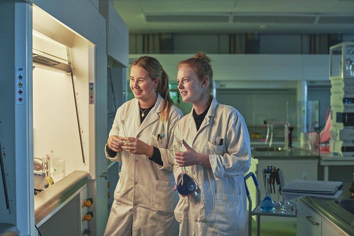 To laborant-studerende står iført kitler og med kolber i hånden i laboratoriet.
