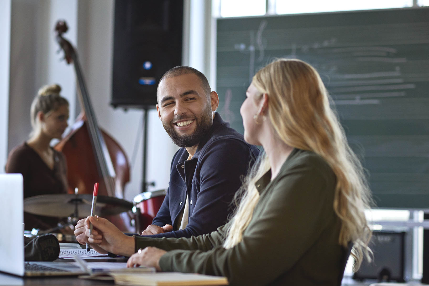 En mandlig og kvindelig lærerstuderende sidder og løser gruppearbejde i et musiklokale