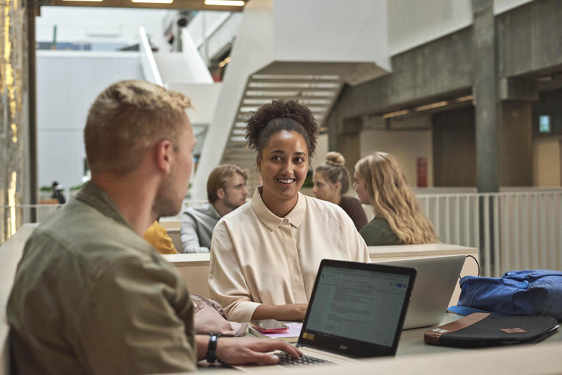 To lærerstuderende løser gruppearbejde ved deres computere på Carlsberg Campus