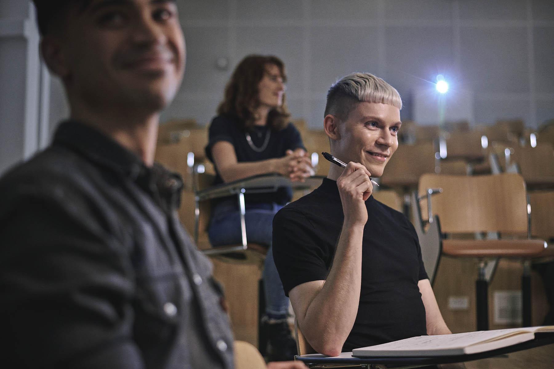 Tre meritpædagog-studerende sidder i et auditorium