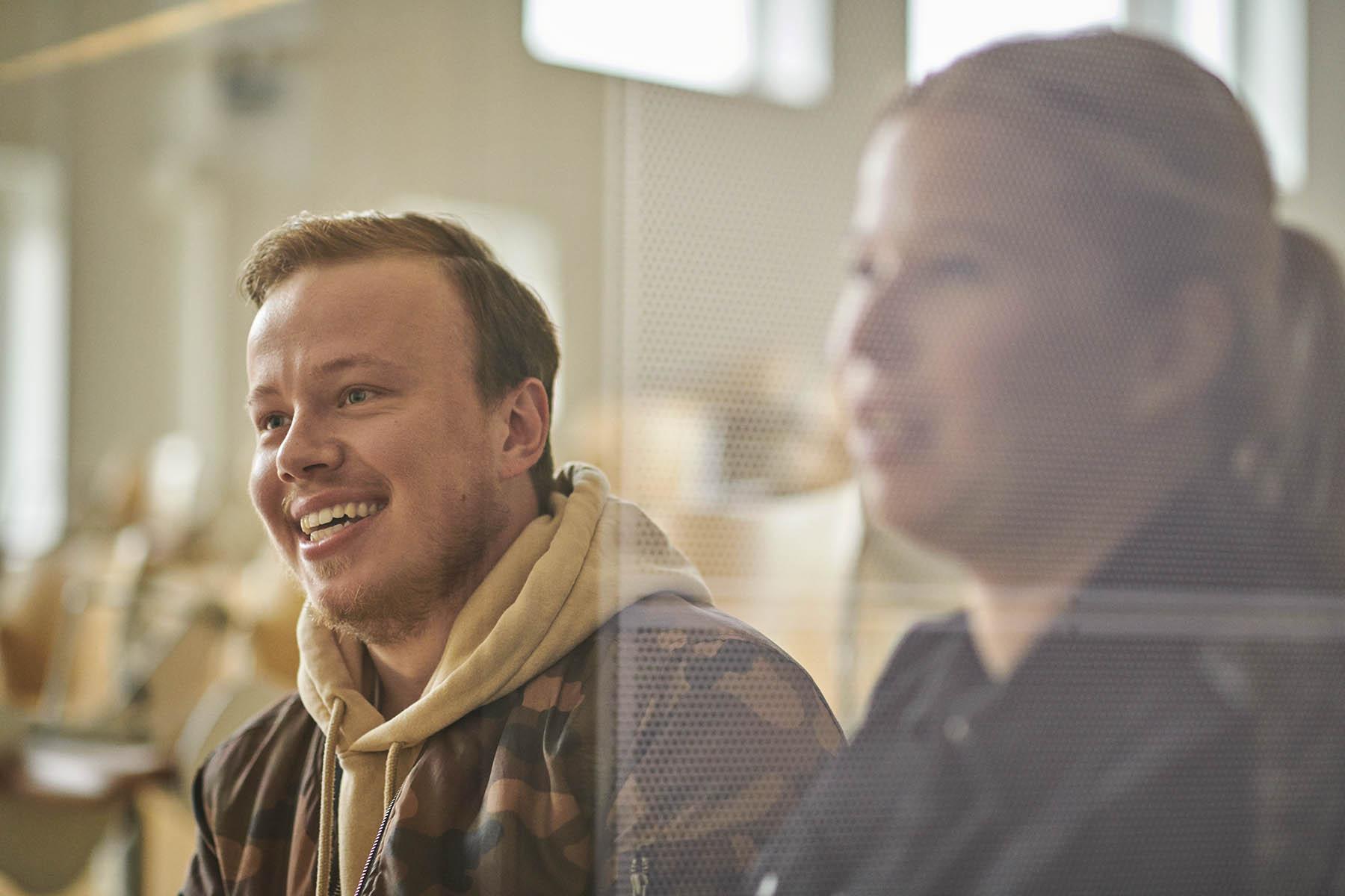 To studerende til pædagogisk assistent sidder i et klasselokale og smiler