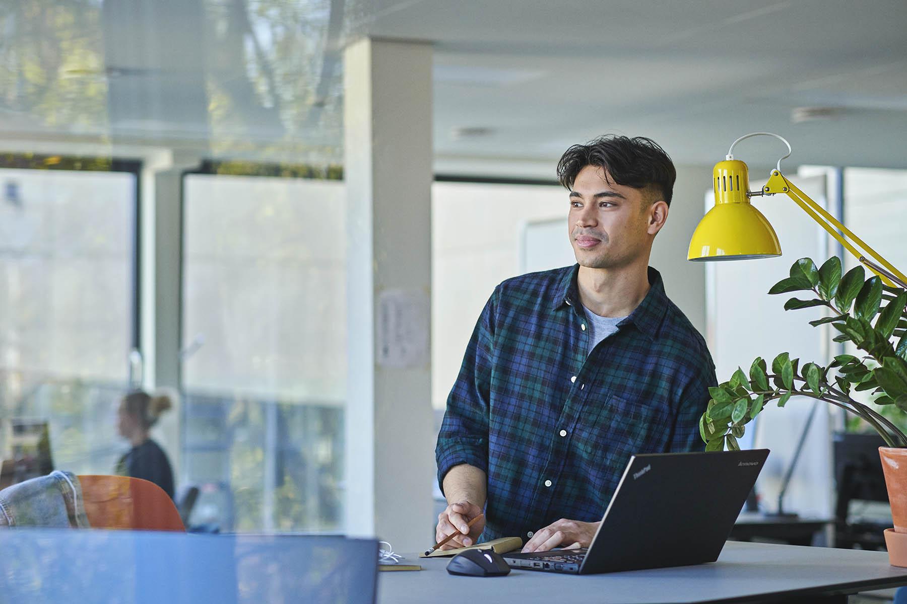 En studerende fra professionsbachelor i skat står ved sin PC