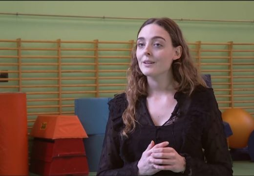 En studerende fra psykomotorisk terapeut fortæller om uddannelsen, mens hun står i en gymnastiksal med redskaber i baggrunden
