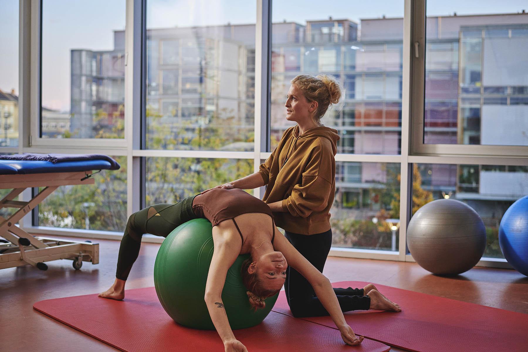 En psykomotorisk terapeut-studerende guider en patient på en gymnastikbold