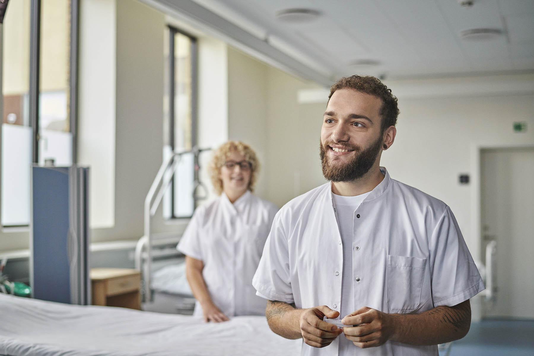 En mandlig og en kvindelig studerende fra sygeplejerskeuddannelsen står iført kitler i hospitalsstuen i Praksis- og Innovationshuset