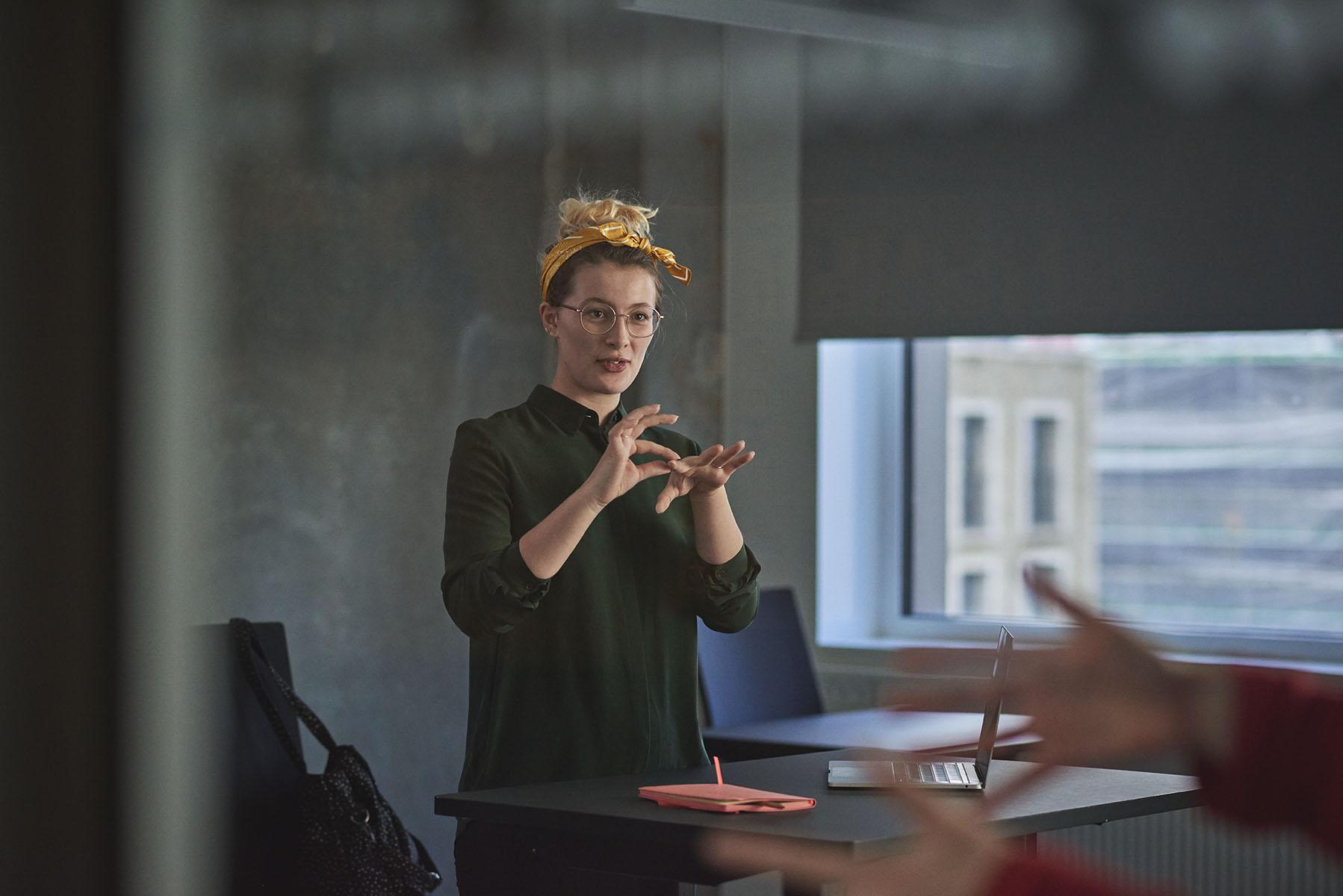 En tegnsprogs- og skrivetolk underviser i tegnsprog i et klasselokale