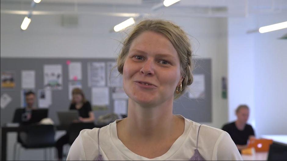 En studerende fra uddannelsen til tegnsprogs- og skrivetolk fortæller om sin uddannelse, mens hun sidder i et klasselokale med medstuderende i baggrunden