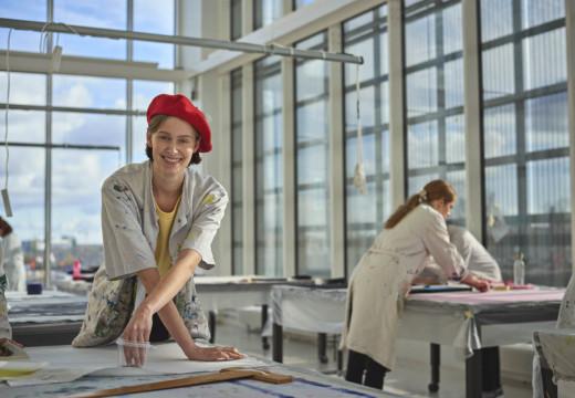 Tekstilformidlerstuderende med rød baskerhue og kittel med malerpletter i trykkeværkstedet