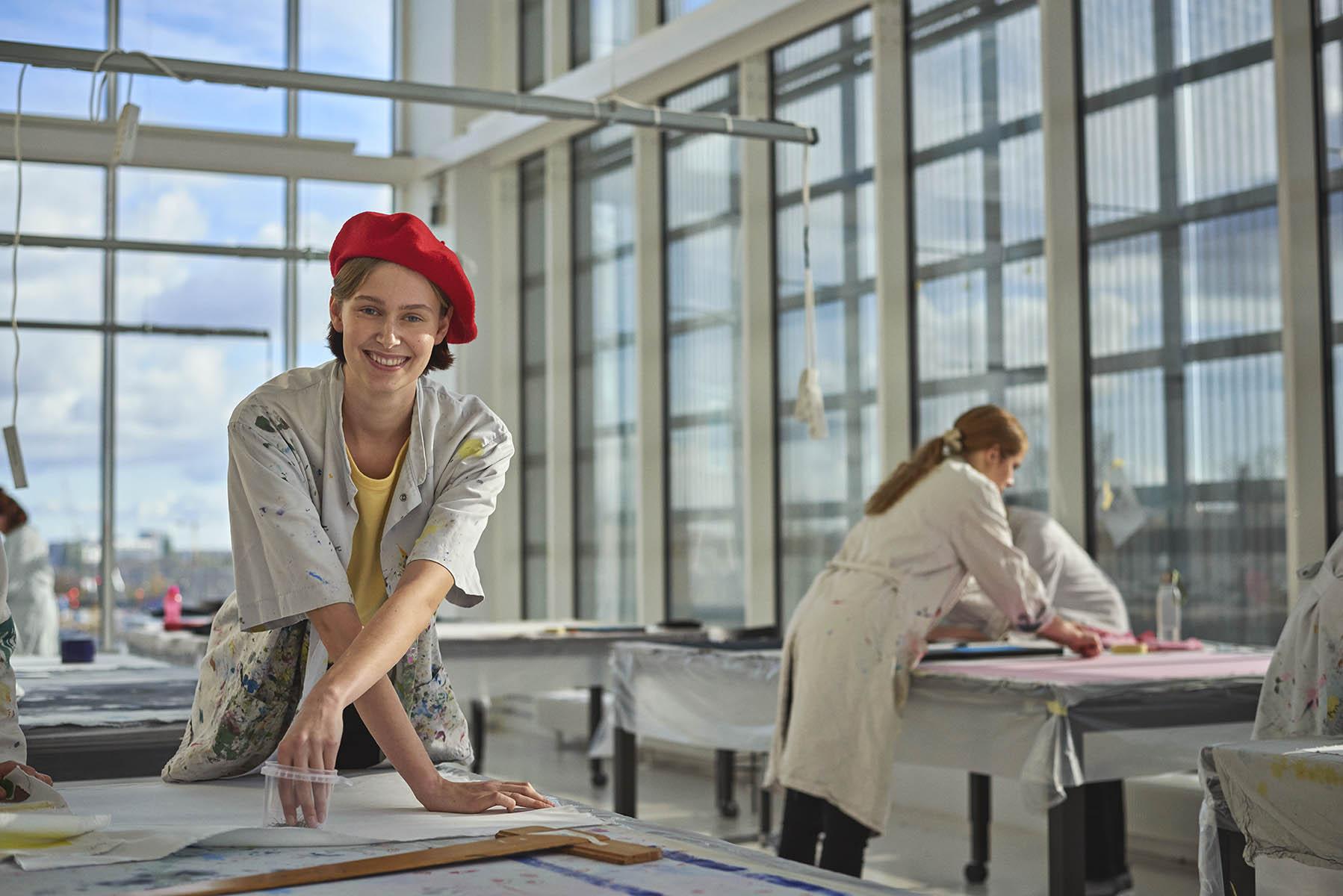 En studerende fra tekstilformidler-uddannelsen står i malerkittel i et lokale på Carlsberg Campus og optegner et mønster