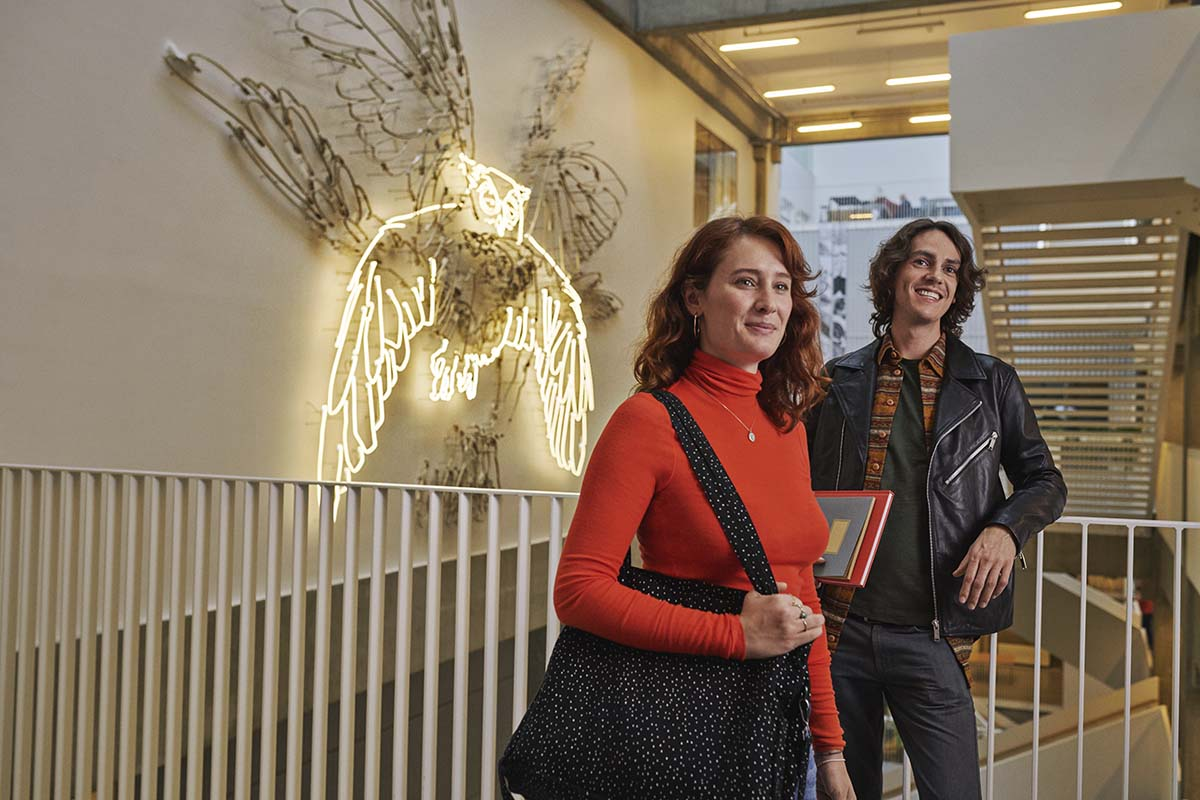 """To studerende, en kvinde og en mand står foran kunstværket """"Orakel"""", som forestiller en ugle og hænger på Calrsberg campus"""