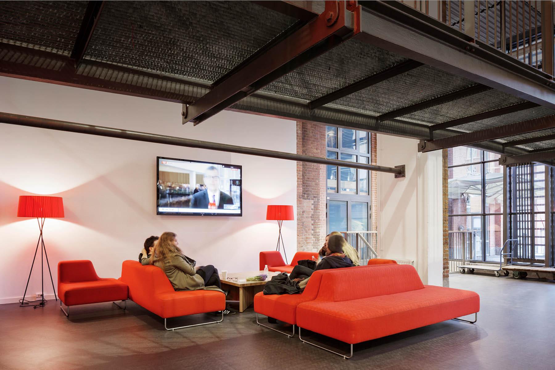 En gruppe studerende sidder og ser nyhederne i nogle orange sofaer på Campus Kronprinsesse Sofies vej