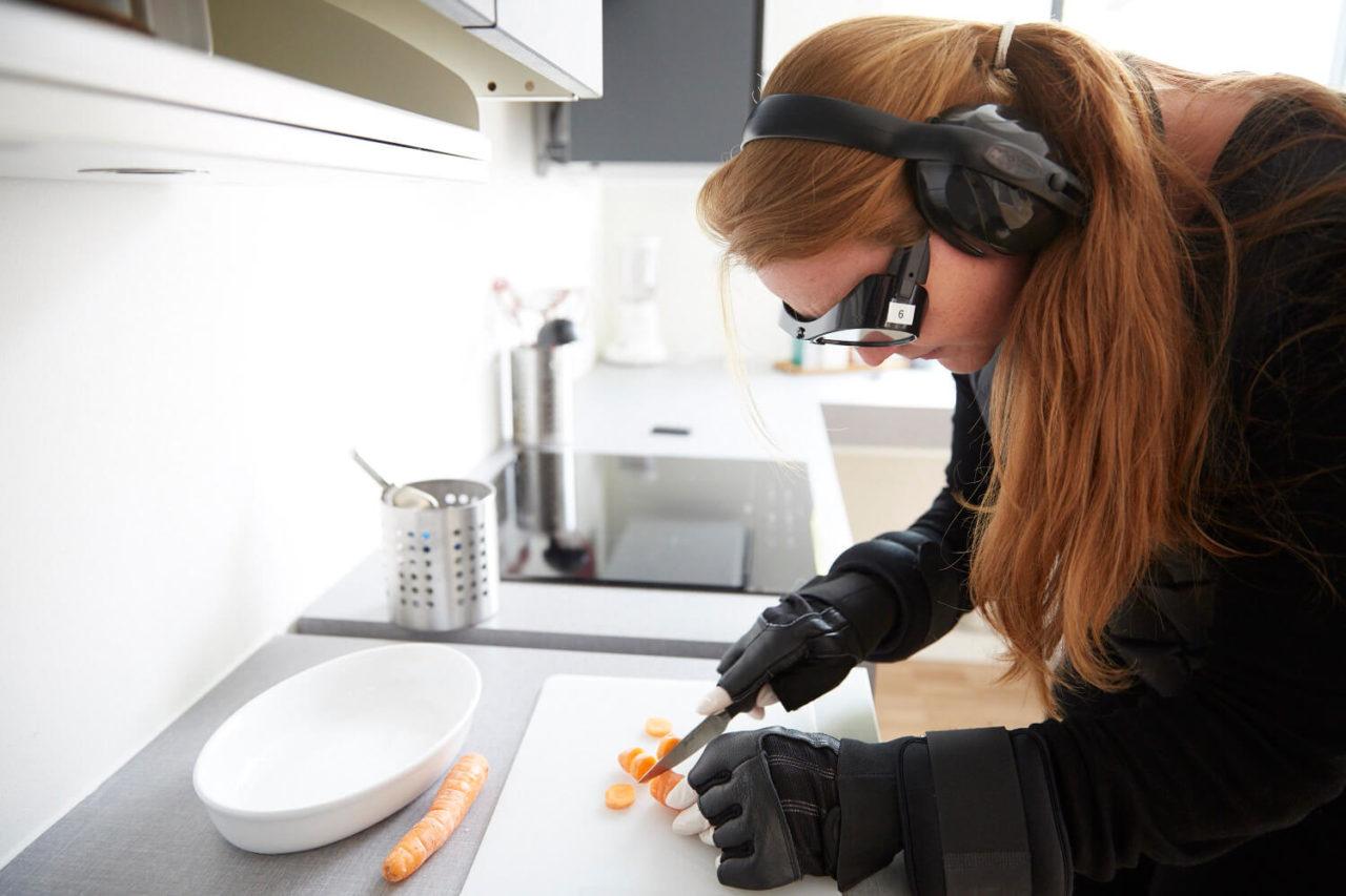 Studerende med bevægelseshæmmende dragt skærer gulerødder