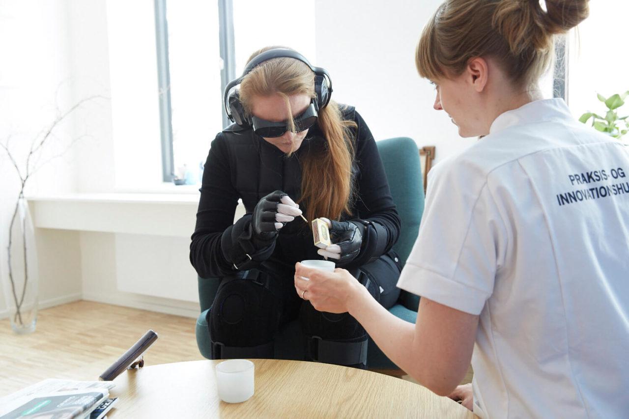 Studerende med bevægelseshæmmende dragt forsøger at stryge en tændstik