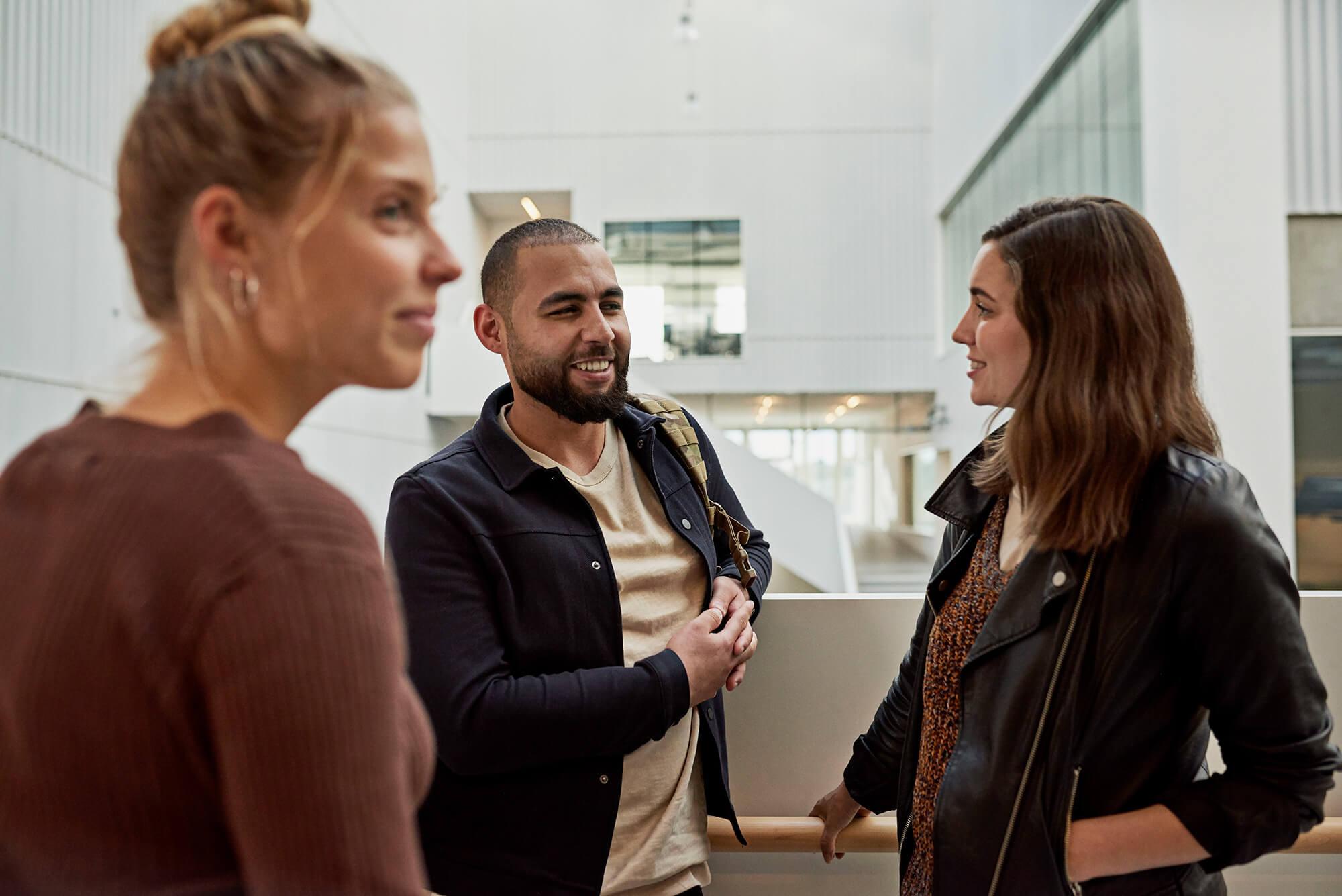 Tre lærerstuderende taler med hinanden ved trappe på Campus Carlsberg
