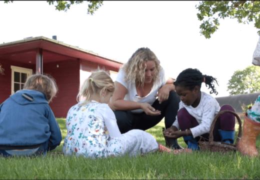 Pædagog sammen med børnehavebørn på græs