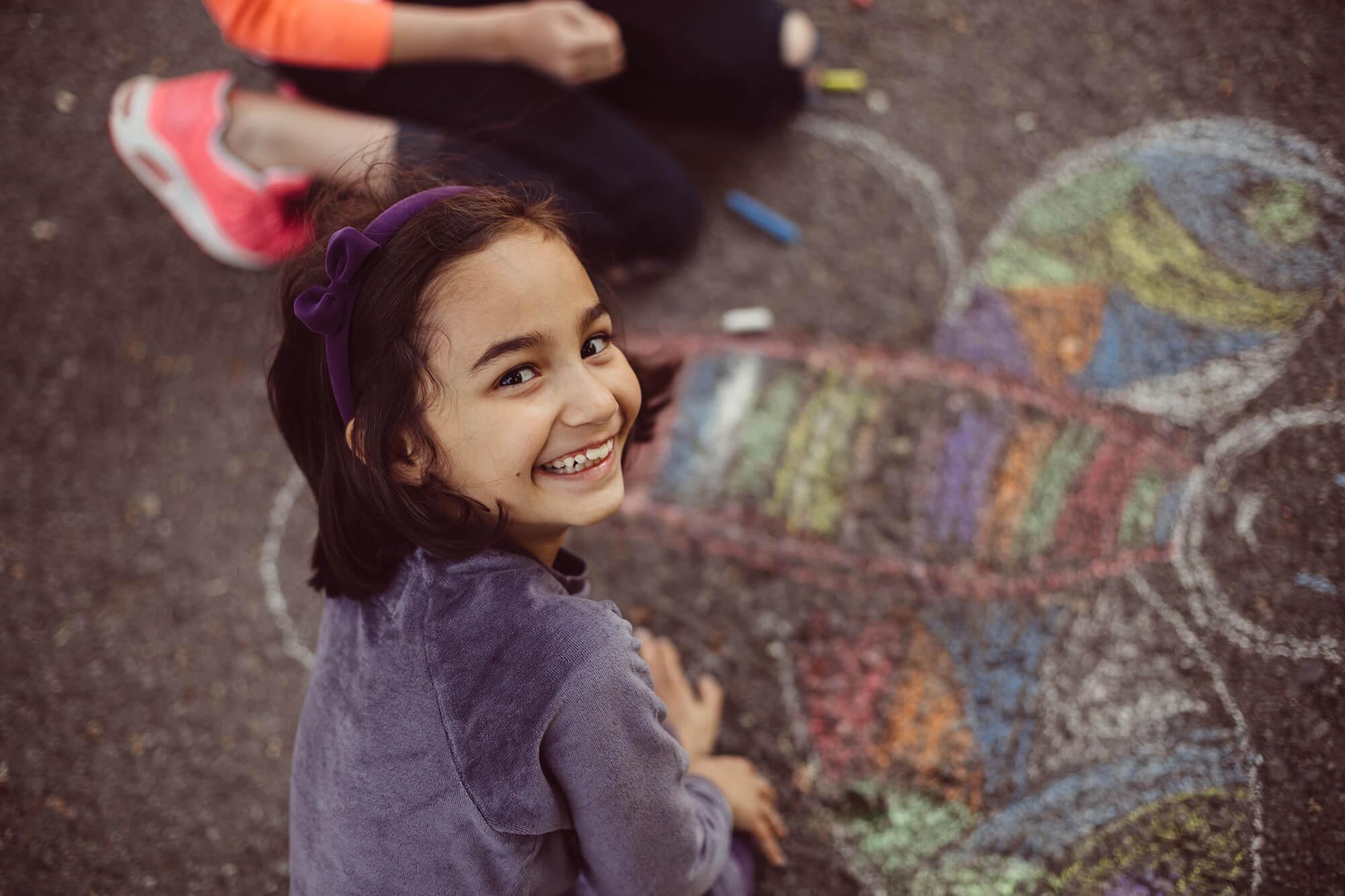 En pige er i gang med at tegne med kridt på asfalten og smiler til kameraet