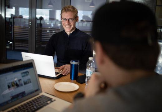 To lærerstuderende med computere ved bord