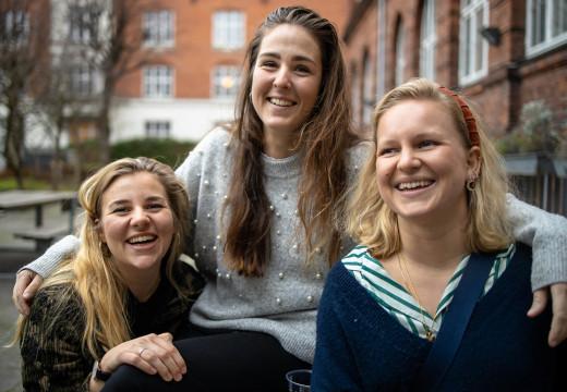 Tre lærerstuderende udendørs smiler til kameraet