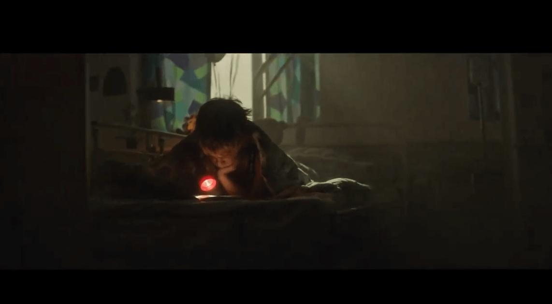 Dreng med lommelygte i seng