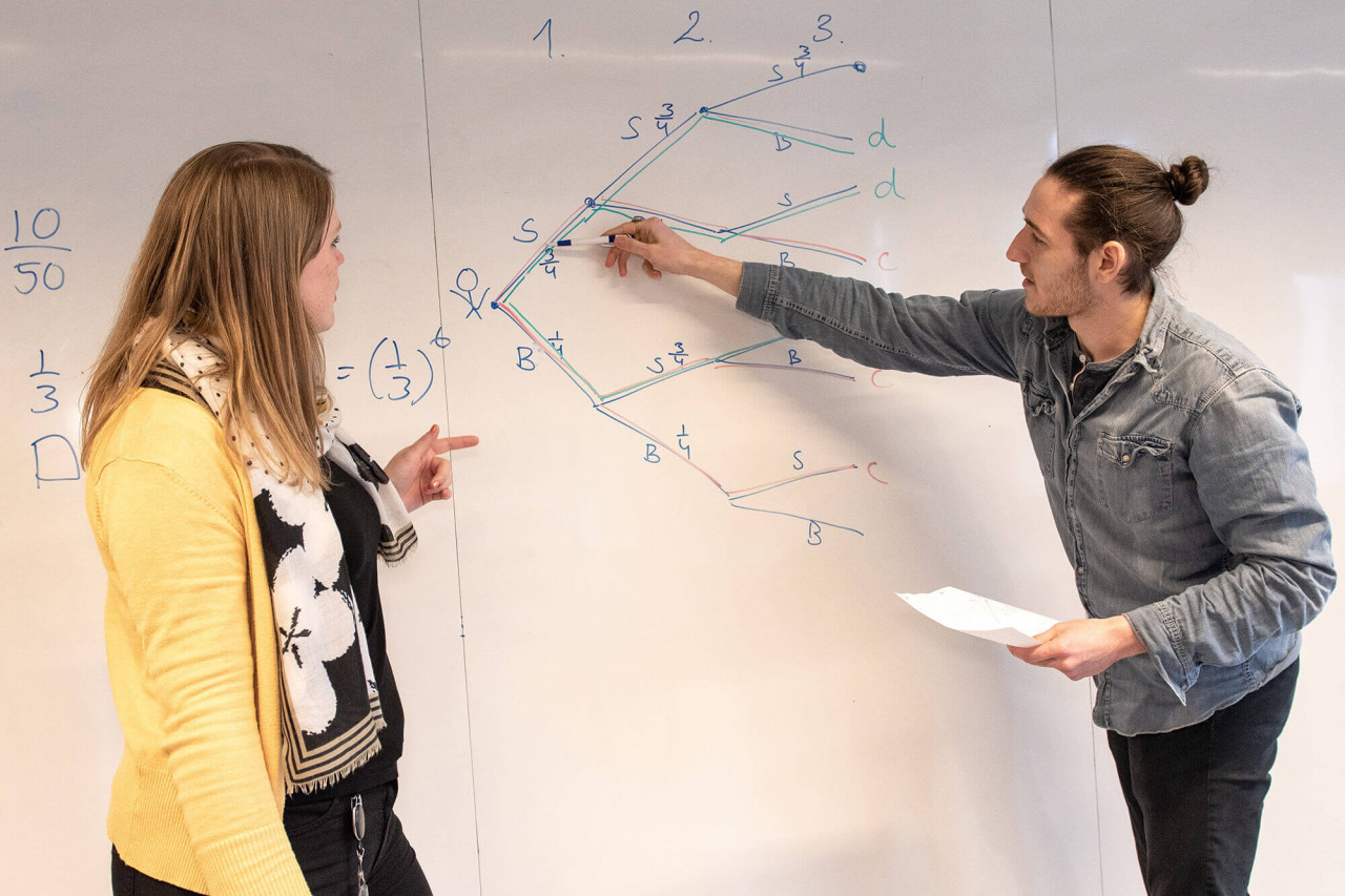 To lærerstuderende laver udregning på whiteboard