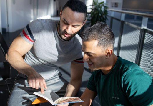To studerende kigger i en bog og snakker