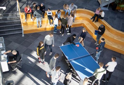 Studerende sidder i fællesareal, nogle spiller bordtennis