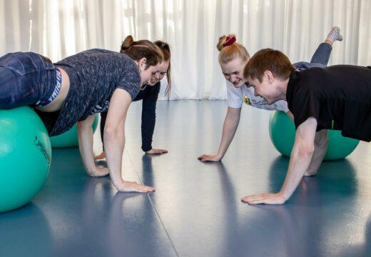 Fire studerende ligger på maven over hver deres træningsbold