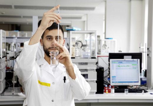 En mandlig laborantstuderende hælder væske i et reagensglas med pipette