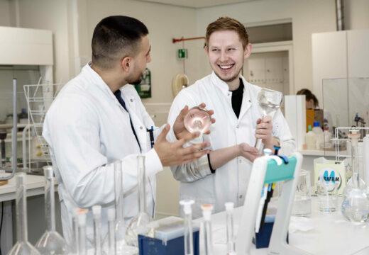 To mandlige laborantstuderende laver gruppearbejde i laboratorium