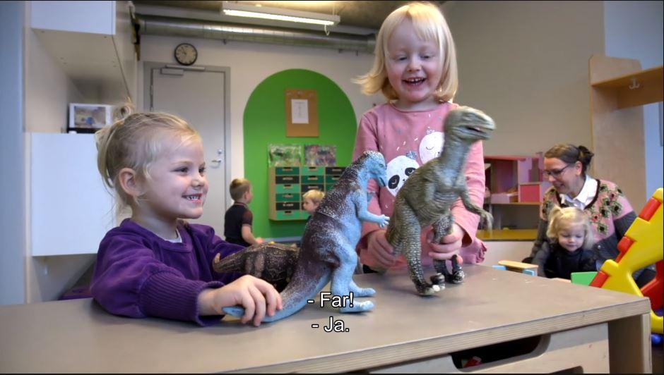 To piger leger med figurer i børnehaven