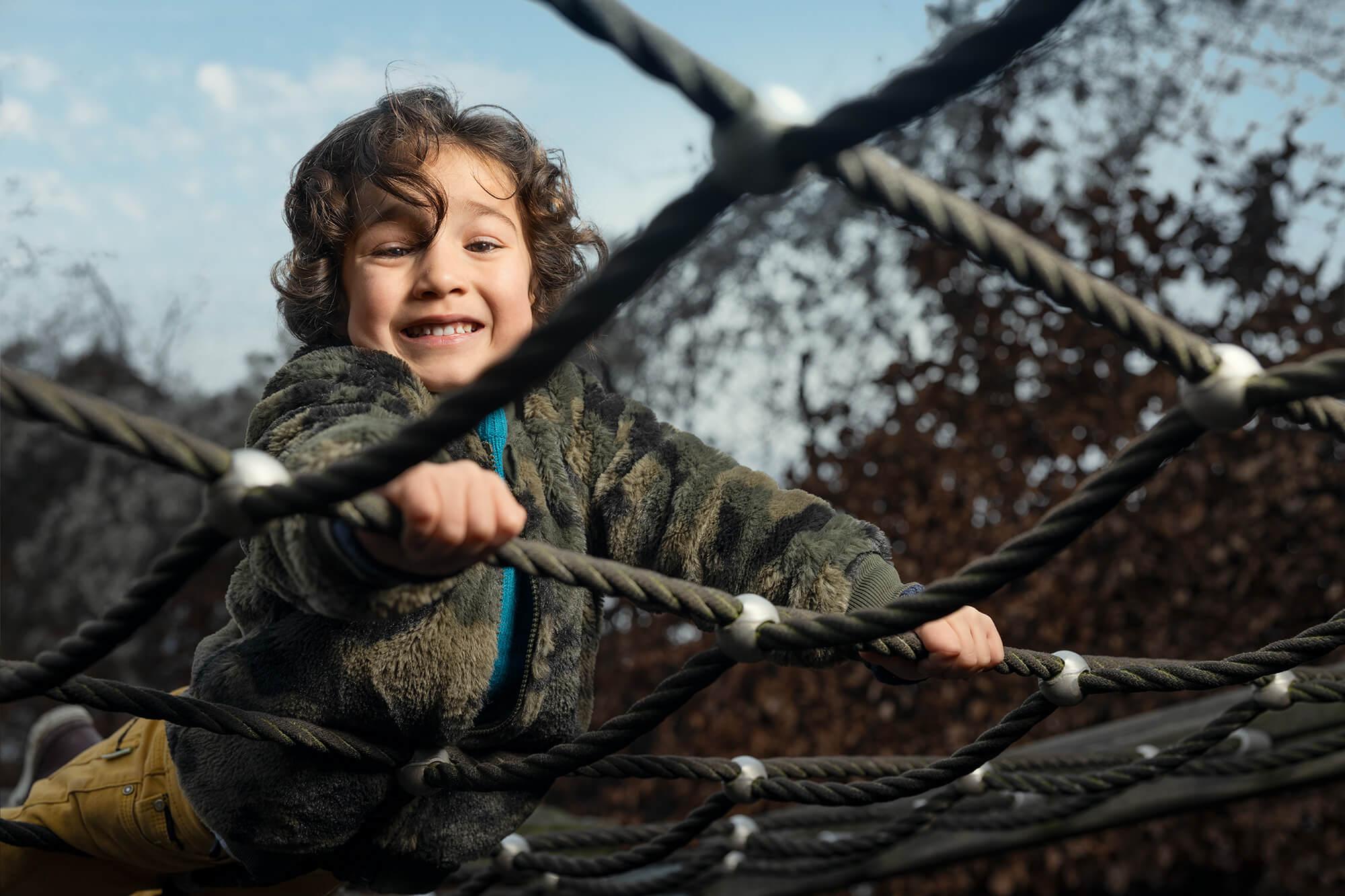 Lille dreng klatrer på et klatrestativ