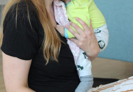 kvinde med baby skriver spørgsmål ned